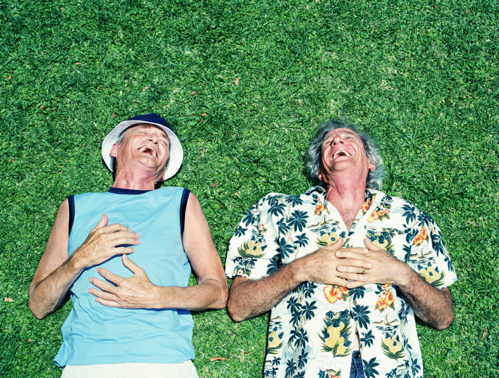 men lying on grass, laughin